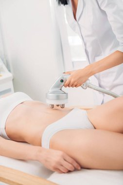 cropped shot of cosmetologist making electrical massage on stomach to female client in white underwear in spa salon