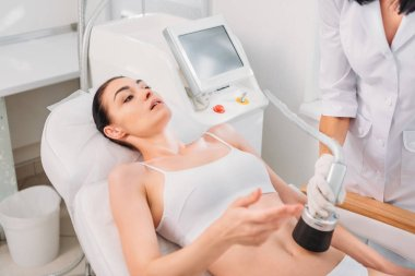attractive woman getting electrical massage made by cosmetologist in spa salon