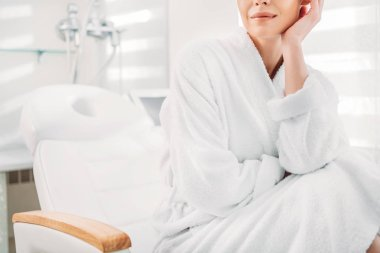 partial view of woman in white bathrobe sitting on massage table in spa salon