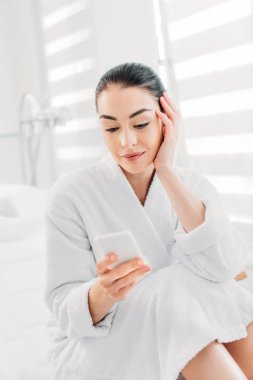 portrait of woman in white bathrobe using smartphone in spa salon
