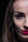 Halbgesicht Porträt eines Vampirs mit roten Augen isoliert auf schwarz