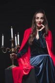 Fotografie Vampir im roten Mantel hält Kandelaber und berühren ihre Zähne isoliert auf schwarz