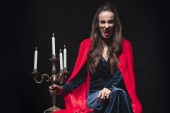 Photo woman in red cloak holding vintage candelabrum and showing vampire fangs isolated on black