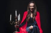 Fotografie Frau im roten Mantel hält Vintage Kandelaber und zeigt Vampir Zähne isoliert auf schwarz