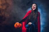 Fotografie schöne Frau in Vampir kostüm lächelnd auf dunklem Hintergrund mit Rauch