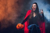 Photo mystic woman in vampire costume holding jack o lantern on darkness with smoke