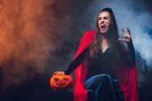 Fotografie mystische Frau in Vampir Kostüm hält Jack-o-Laterne auf Dunkelheit mit Rauch