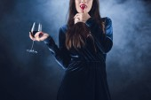 Fotografie cropped view of vampire holding wineglass with blood and licking her fingers on dark background with smoke