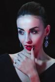 Fotografie attraktiven Vampir berührt ihre Lippen isoliert auf schwarz