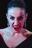 grimmiger Vampir blickt auf Kamera isoliert auf Schwarz