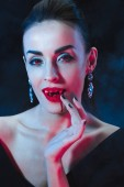 Fotografie sexy Vampir Frau leckt ihre Finger auf dunklem Hintergrund mit Rauch