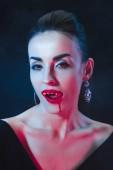 Fotografie sexy Vampir Frau lecken ihre Lippen auf dunklem Hintergrund
