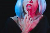 abgeschnittene Ansicht von Vampirfrau leckt ihren Mittelfinger isoliert auf schwarz