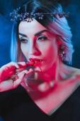 Fotografie sexy Vampir Frau lecken blutige Finger auf Dunkelheit mit Rauch