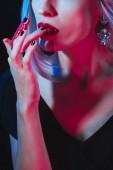 Ausgeschnittene Ansicht eines Vampirs, der ihre Finger auf dunklem Hintergrund mit Rauch leckt