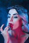 Fotografie sexy Vampir Frau leckte Blut vom Finger auf dunklem Hintergrund mit Rauch