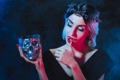 beautiful vampire woman holding metal skull with blood and licking her fingers isolated on black