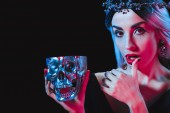 vampire holding metal skull with blood and licking her fingers isolated on black