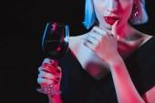 Fotografie sexy Vampir Frau hält Weinglas mit Blut und berührt ihre Lippen isoliert auf schwarz