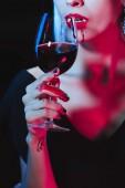 abgeschnittene Ansicht eines Vampirs, der Blut aus einem Weinglas trinkt, isoliert auf schwarz