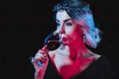 sexy Vampir trinkt Blut aus Weinglas isoliert auf schwarz