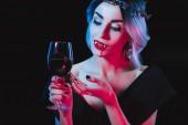 Fotografie sexy Vampir Frau mit Weinglas mit Blut isoliert auf schwarz