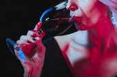 abgeschnittene Ansicht einer Vampirfrau, die Blut aus einem Weinglas trinkt, isoliert auf schwarz