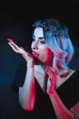 attraktiver Vampir leckt Blut aus der Hand auf dunklem Hintergrund mit Rauch