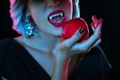 abgeschnittene Ansicht von Vampir beißt roten blutigen Apfel isoliert auf schwarz