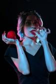 Vampirfrau mit rotem blutigen Apfel leckt ihre Finger isoliert auf schwarz