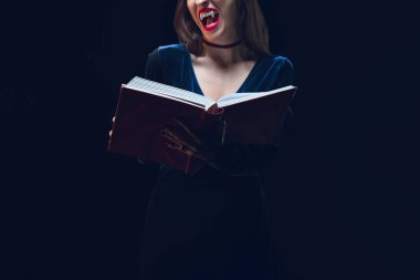 Cropped view of vampire woman holding magic book isolated on black