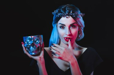 vampire woman holding skull with blood and licking her fingers isolated on black