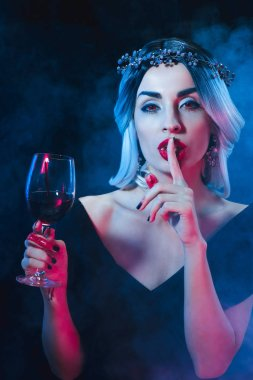 sexy vampire woman showing silence symbol and holding wineglass with blood on dark background with smoke
