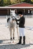 Fotografia bello maschio equestre fissaggio cavallo cavezza al horse club