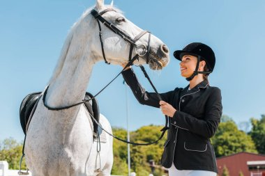 attractive female equestrian palming horse at horse club