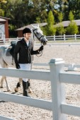 Fotografie smiling handsome male equestrian walking near horse at horse club