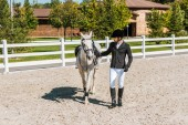 Fotografie handsome male equestrian walking near horse at ranch
