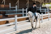 Photo handsome male equestrian riding horse at horse club
