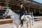 handsome male equestrian riding white horse at horse club