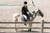 side view of handsome male equestrian in professional apparel sitting on horse at ranch and looking away