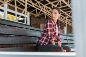 Fotografie beautiful cowgirl in checkered shirt sitting on bench at ranch stadium and looking away