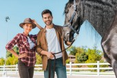 Photo smiling female and male equestrians standing near horse at ranch and looking at camera