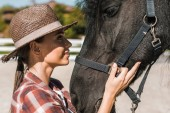 Fotografia Ritratto di attraente femminile equestre toccando e guardando il cavallo al ranch