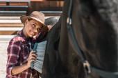 krásnou usměvavou jezdecké čištění černého koně s kartáčem na ranči
