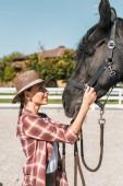 Fényképek oldalnézetből a vonzó cowgirl kalapját rögzítő kötőfék ló Ranch