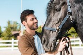 Fotografie smiling handsome cowboy fixing horse halter at horse club