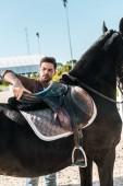 Fotografie hezký kovboj stanovení sedlo koně na ranči