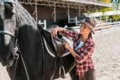 atraktivní žena krotící koně v kostkované košili stanovení sedlo koně na ranči