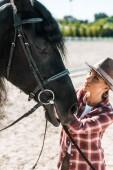 Krásné ženské jezdecké v kostkované košili a klobouk stanovení ohlávku koně na ranči