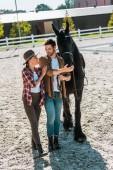 šťastné ženské a mužské jezdci s koně na ranči